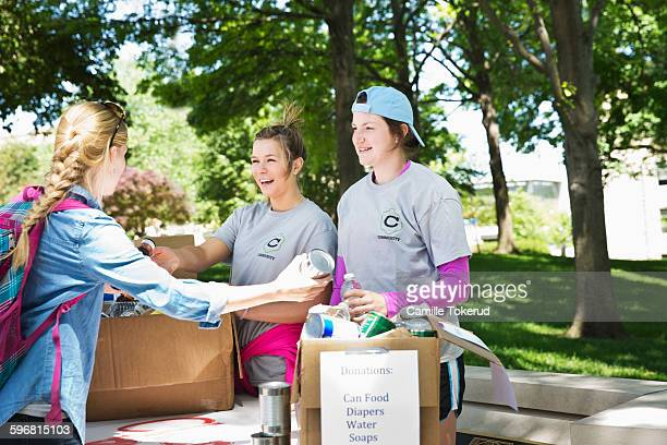 college students collecting food in a food drive - charity benefit stock pictures, royalty-free photos & images