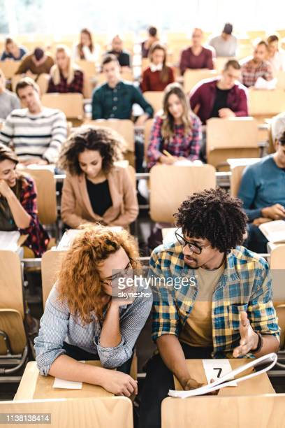 college students cooperating while reading a lecture on a class. - college students stock pictures, royalty-free photos & images
