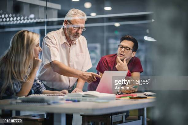 college students cooperating with their professor while e-learning at campus. - small group of people stock pictures, royalty-free photos & images