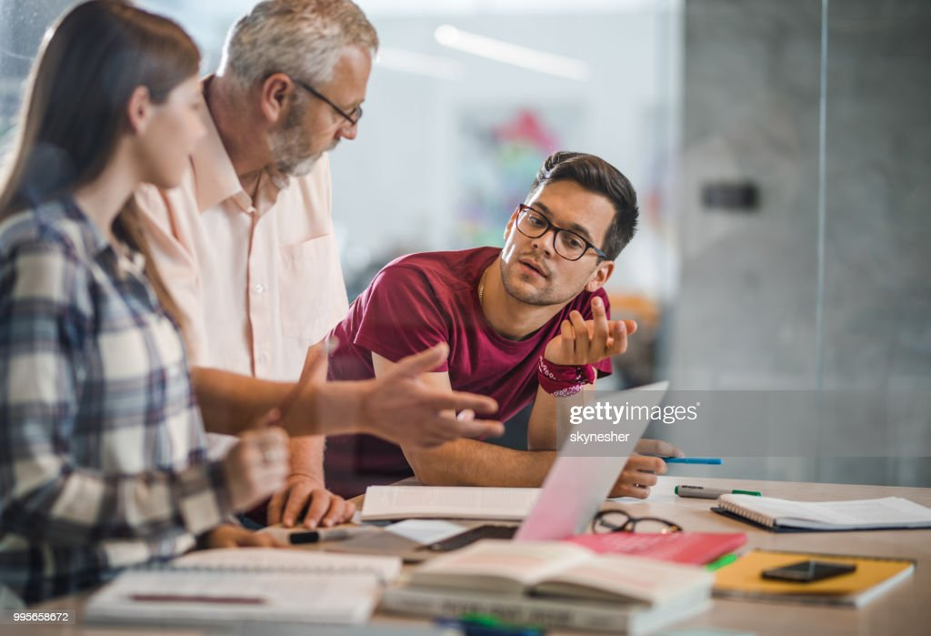 College students cooperating with their professor while e-learning at campus. : Stock Photo