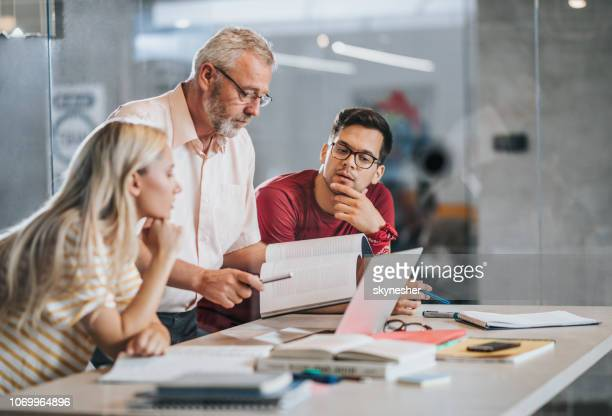 college students cooperating with their professor while studying at campus. - professor stock pictures, royalty-free photos & images