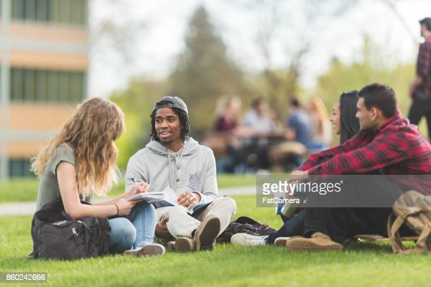 College students hang out in between classes and study on the grass