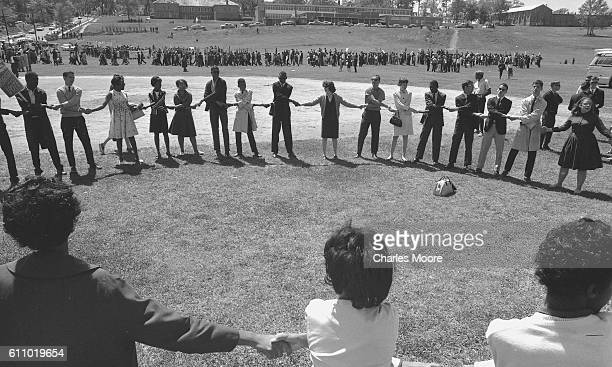 College students hold hands in a large circle during a Civil Rights demonstration on the campus of Florida State University Tallahassee Florida March...