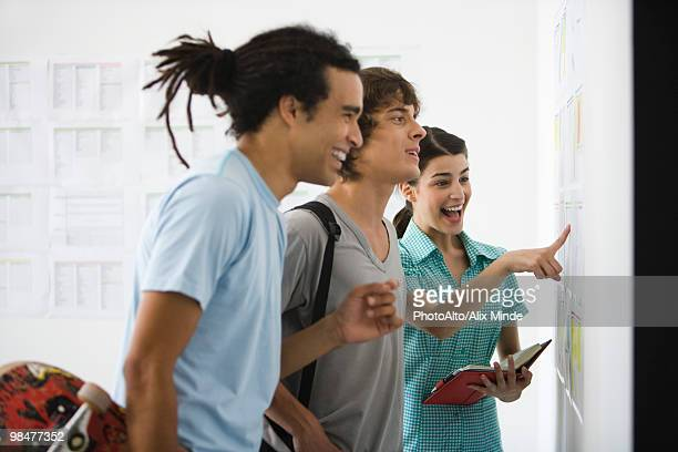 College students looking with pleased expressions at results posted on bulletin board