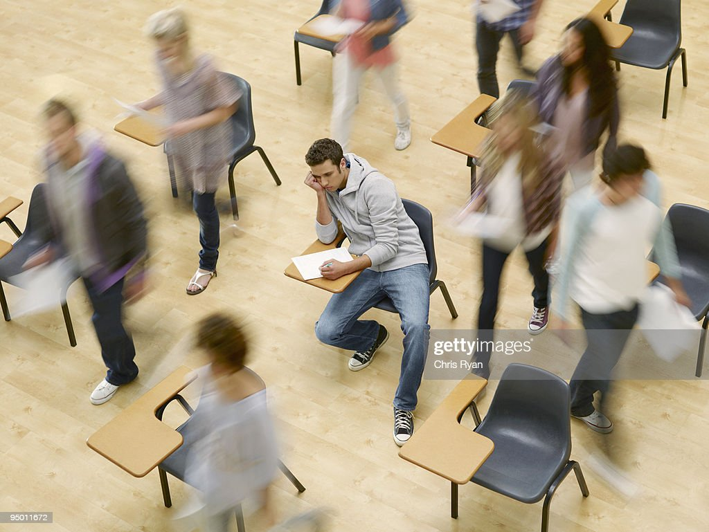 College students moving around man at desk in classroom : Stock Photo