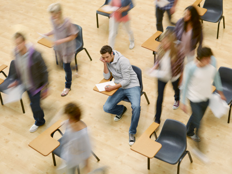 College students moving around man at desk in classroom - gettyimageskorea