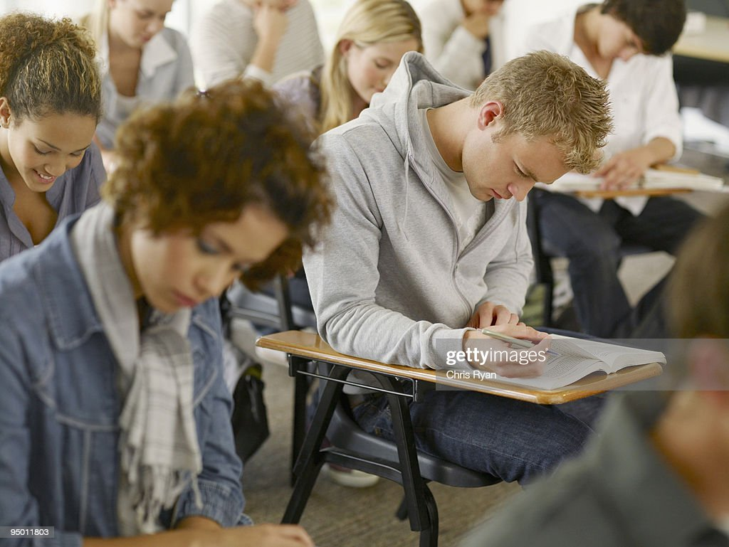 College students reading at desks in classroom : Stock Photo
