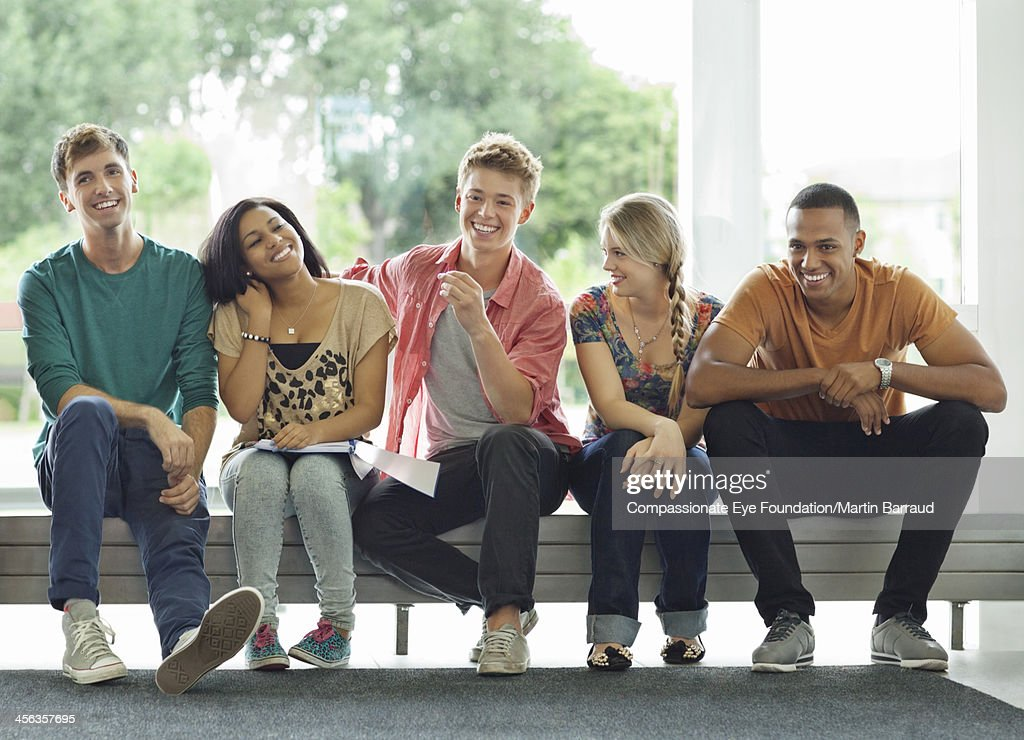 College students relaxing in hallway : Stock Photo
