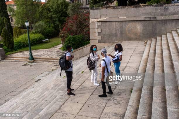 los estudiantes universitarios regresan al campus con máscaras protectoras - devolución del saque fotografías e imágenes de stock