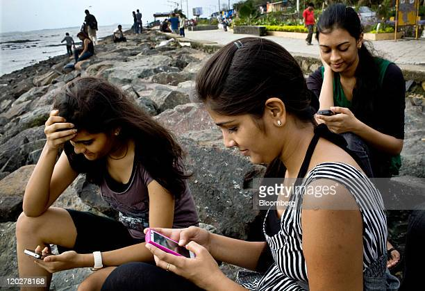 College students Saloni Shah from left Roshani Munat 18 and Shruti Jain check Facebook Inc accounts on smartphone devices in Mumbai India on...
