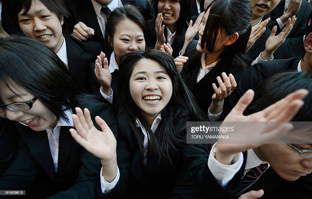 College students shout as they clap their hands at the start of a job hunting ceremony in Tokyo on February 13, 2013. Some 1,500 students, who will graduate from schools in March 2014, attended the annual ceremony which aims to encourage future graduates to look for jobs. AFP PHOTO/Toru YAMANAKA