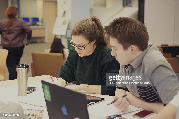 College students sit at a table studying together in the Brody Learning Commons a interactive/collaborative study space and library on the Homewood...