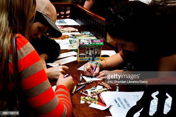 College students sit at an old wooden desk coloring bookmarks with crayons at the Baltimore Book Festival a large festival where authors and readers...