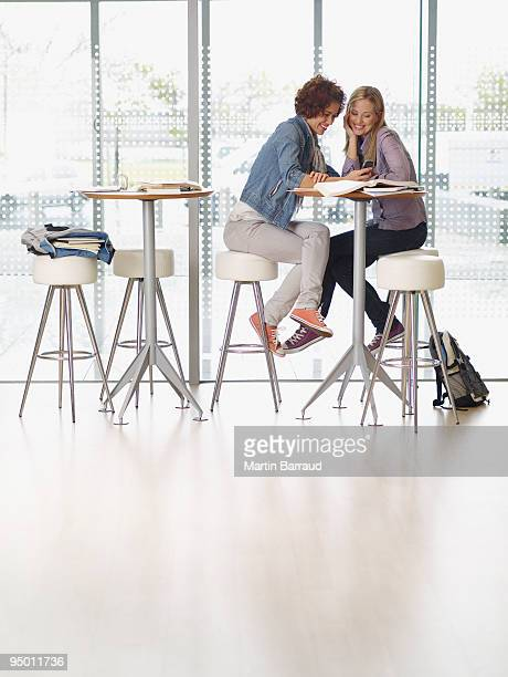 College students sitting at table using cell phone