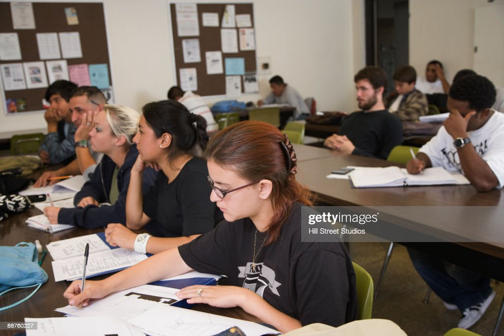 college students sitting at tables in classroom ストックフォト