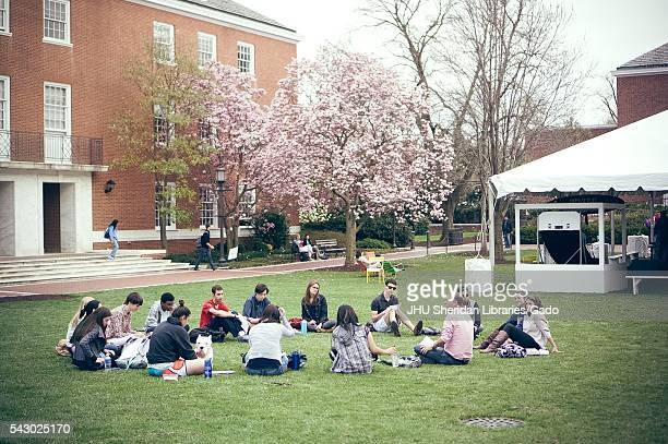 College students sitting in a circle on Johns Hopkins University's Wyman Quad, a social gathering area for college students in front of Shriver Hall,...