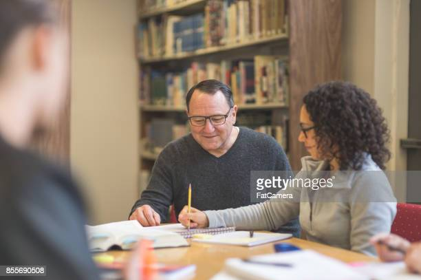 college students study together around a table in the library - master's degree stock pictures, royalty-free photos & images