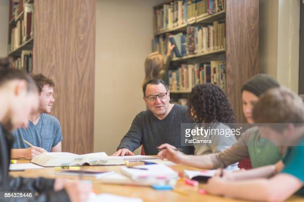 College students study together around a table in the library