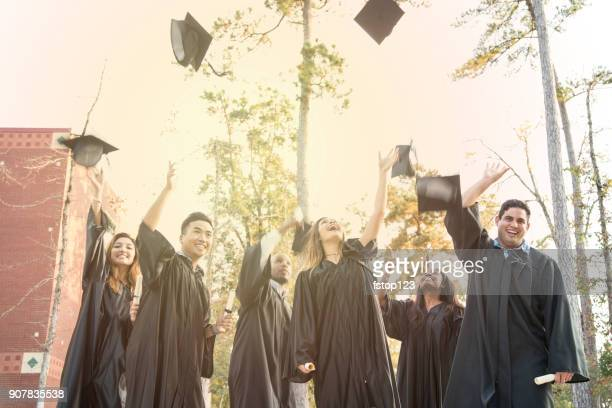 college-studenten werfen kappen in luft nach abschlussfeier. - feierliche veranstaltung stock-fotos und bilder