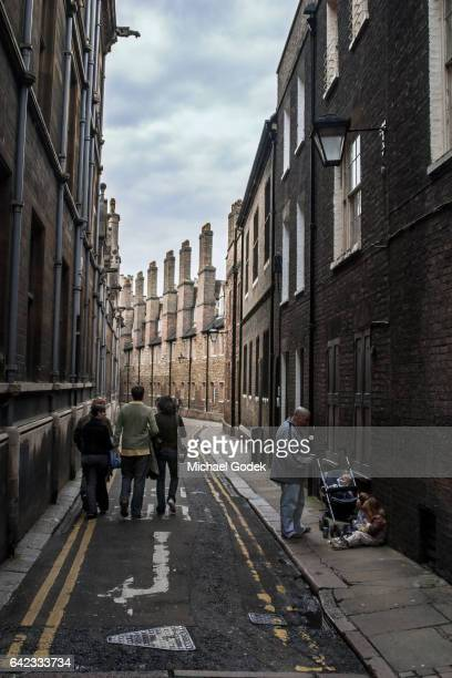 College students walk down the unique winding Trinity Ln. in Cambridge University UK
