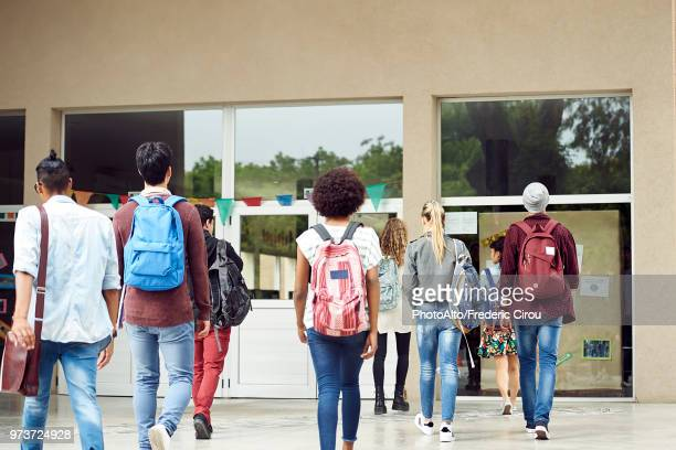 college students walking on campus, rear view - back to school stock pictures, royalty-free photos & images