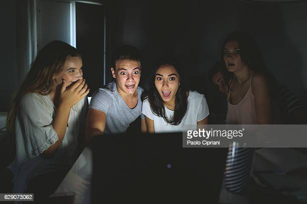 college students watching scary movie on laptop - scary movie stock photos and pictures