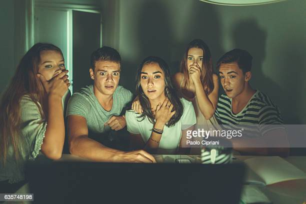 college students watching scary movie on laptop - scary face stock photos and pictures