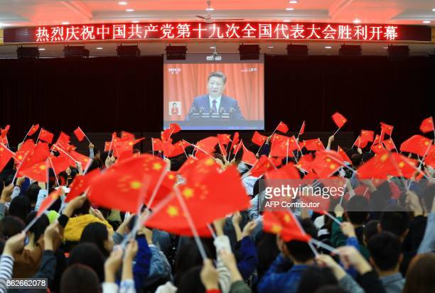 College students wave national flags as they watch the opening of the 19th Communist Party Congress in Huaibei in China's eastern Anhui province on...