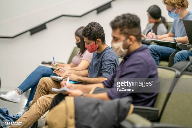 college students wearing masks in a lecture hall - fatcamera stock pictures, royalty-free photos & images