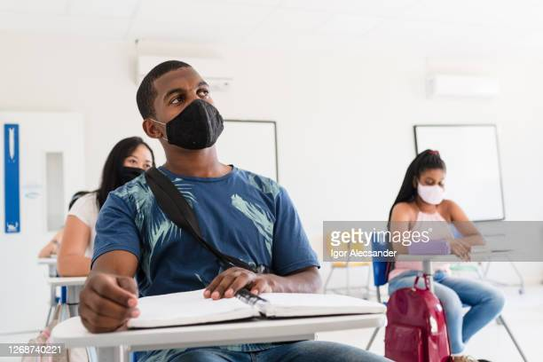 college students wearing protective mask in the classroom - college student stock pictures, royalty-free photos & images