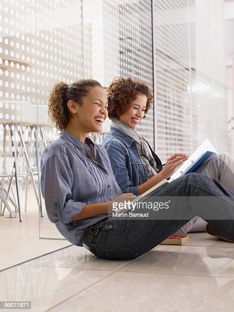 大学生、ノートブック床に座ると笑う