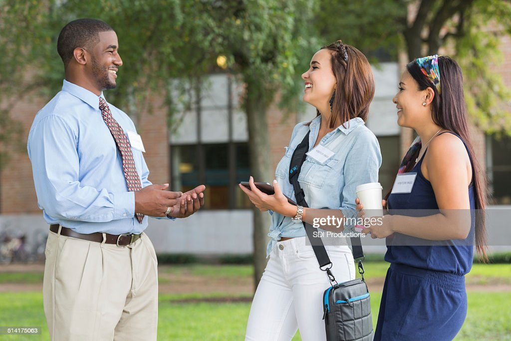 College tour guide talking with visiting students on campus : Stock Photo