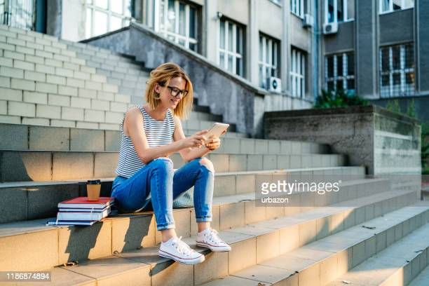 college woman using tablet - literature stock pictures, royalty-free photos & images