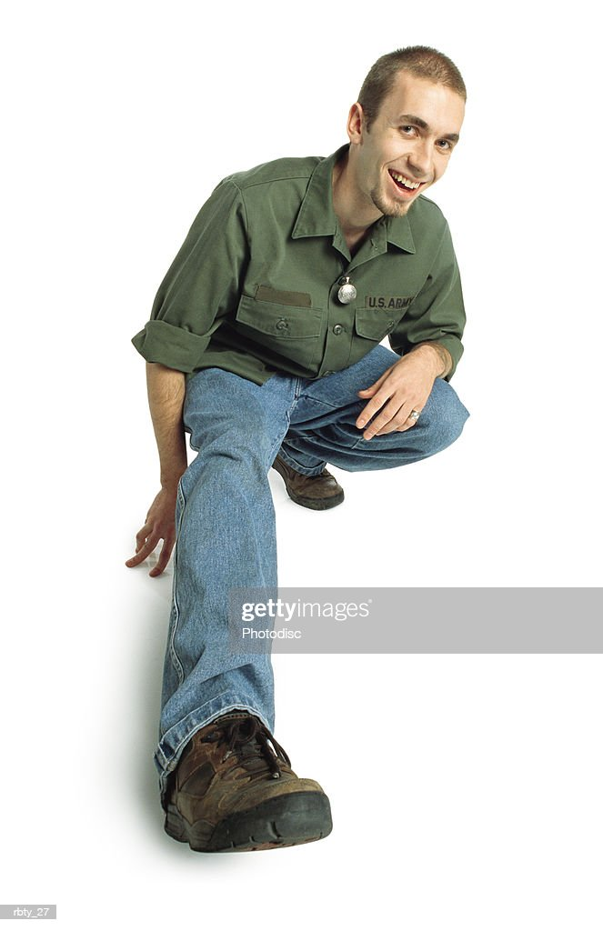 college-age young man with a small beard and short hair wearing a green army shirt blue jeans and brown shoes squats down and sticks one foot out towards the camera and smiles : Foto de stock