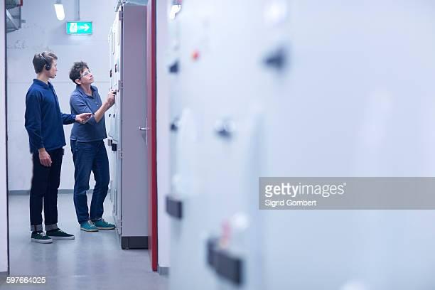 colleges in control room looking at switchgear - sigrid gombert fotografías e imágenes de stock