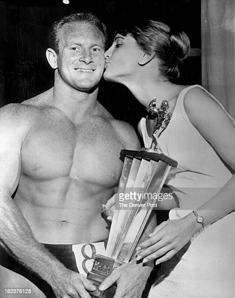JUN 14 1960 Collegian Named Mr America Lloyd Lerille 24yearold New Orleans college student receives a trophy and kiss from Bonnie Raymond after his...