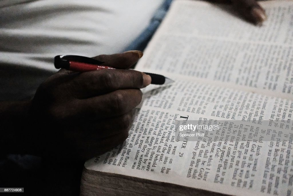 Collen Harris, a practicing Muslim and a displaced resident from the island of Barbuda, reads the Bible to pass time inside a shelter at a cricket stadium on December 7, 2017 in St John's, Antiqua. Barbuda, which covers only 62 square miles, was nearly leveled when Hurricane Irma made landfall with 185mph winds on the night of September 6. Only two days later, fearing Barbuda would be hit again by Hurricane Jose, the prime minister ordered an evacuation of all 1,800 residents of the island. Most are now still in shelters scattered around Barbuda's much larger sister island Antigua.