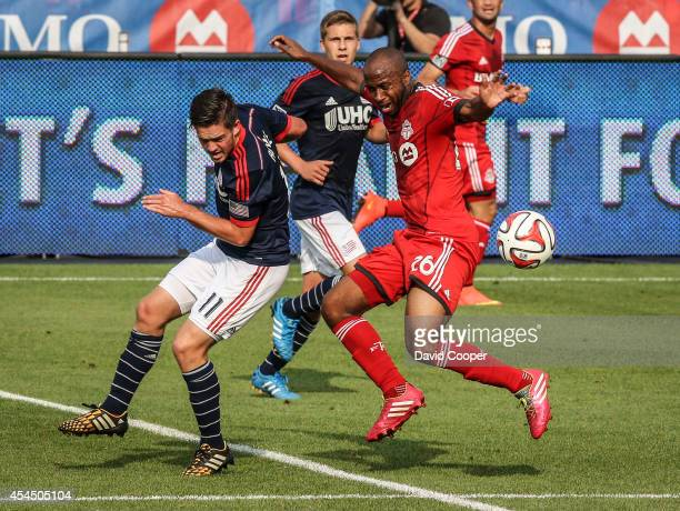 Collen Warner of TFC fights for the ball with Kelyn Rowe of the Revolution during the game between Toronto FC and New England Revolution at BMO Field