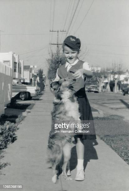 A collie stands on its hind legs in order to get a treat from a young girl circa 1952
