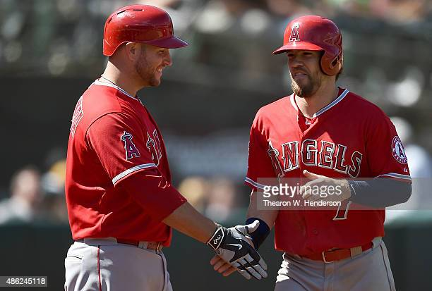 Collin Cowgill of the Los Angeles Angels of Anaheim is congratulated by Chris Iannetta after Cowgill scored against the Oakland Athletics in the top...