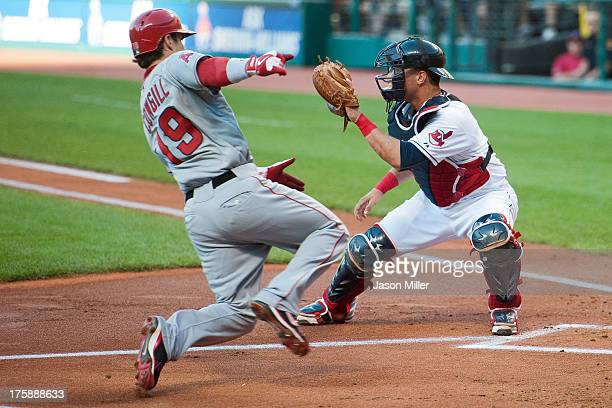 Collin Cowgill of the Los Angeles Angels of Anaheim slides into home plate as catcher Yan Gomes of the Cleveland Indians waits for the throw during...