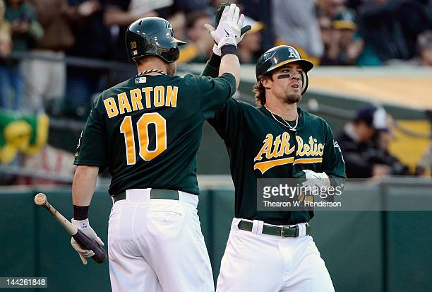 Collin Cowgill of the Oakland Athletics is congratulated by Daric Barton after scoring on a RBI triple from Cliff Pennington in the seventh inning...