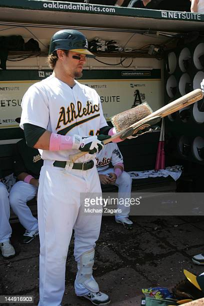 Collin Cowgill of the Oakland Athletics runs pinetar on his bat handle in the dugout during the game against the Detroit Tigers at the OaklandAlameda...