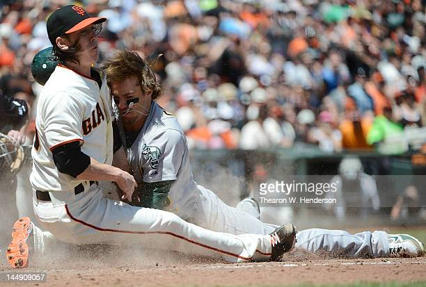 Collin Cowgill of the Oakland Athletics scoring from second base on a wild pitch collides at homeplate with pitcher Tim Lincecum of the San Francisco...