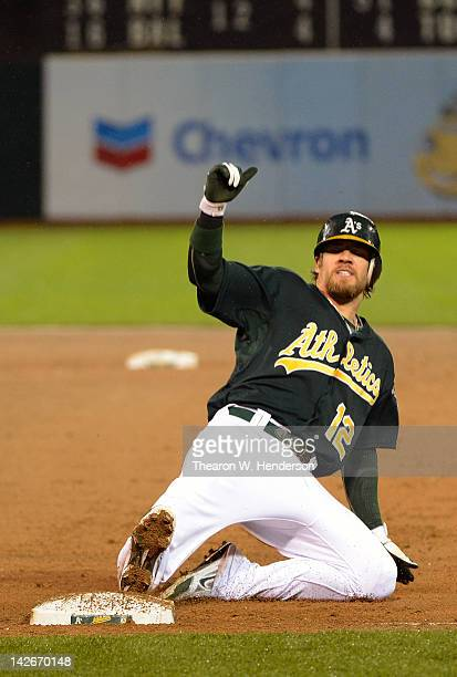 Collin Cowgill of the Oakland Athletics slides back into first base but is doubled off in the second inning against the Kansas City Royals at Oco...