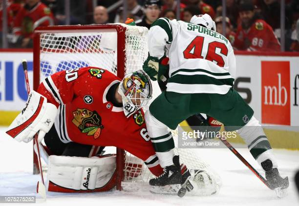 Collin Delia of the Chicago Blackhawks makes a stop against Jared Spurgeon of the Minnesota Wild at the United Center on December 27 2018 in Chicago...