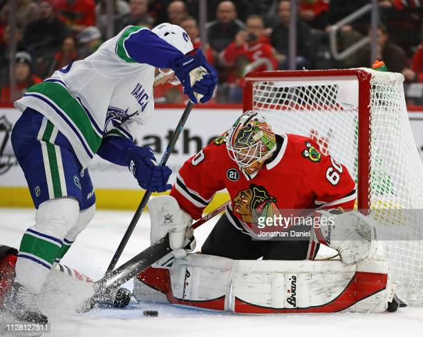 Collin Delia of the Chicago Blackhawks stops a shot by Bo Horvat of the Vancouver Canucks at the United Center on February 07 2019 in Chicago Illinois