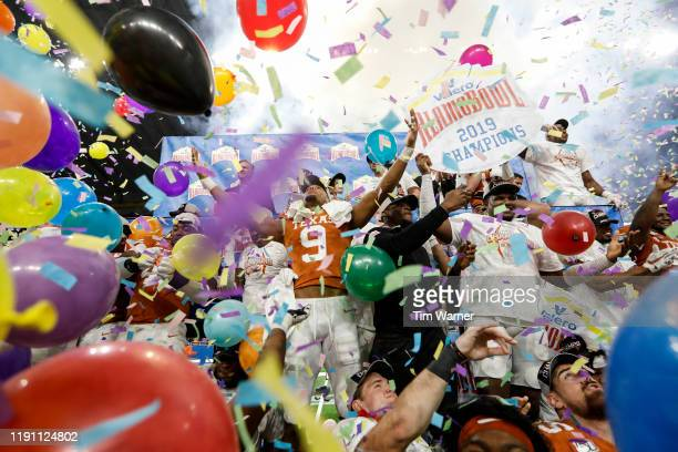 Collin Johnson of the Texas Longhorns celebrates with teammates during the trophy presentation after the Valero Alamo Bowl game against the Utah Utes...