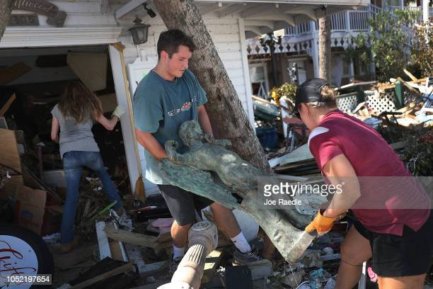 Collin Jorey helps Brandy Wood Jessen carry an angel statue as they salvage items from her parents Driftwood Inn that was severely damaged by...