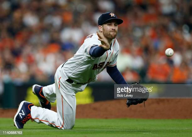 Collin McHugh of the Houston Astros flips the ball to first base on a slow ground ball by Marcus Semien of the Oakland Athletics in the fourth inning...